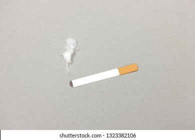 Minimalist paper cutout of cigarette with fume made of cotton composed on gray background