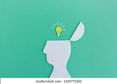 Minimalist paper cutout of man with burning light bulb in opened head on green background