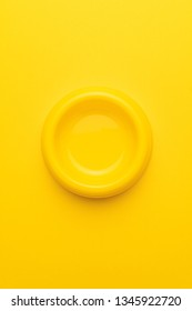 minimalist photo of empty yellow pet bowl on the yellow background