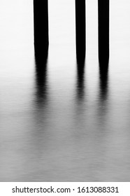 Minimalist photo of pier and pylons and water near sunset, made using long exposure