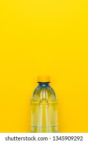 minimalist photo of plastic water bottle with yellow cap on the yellow background with copy space