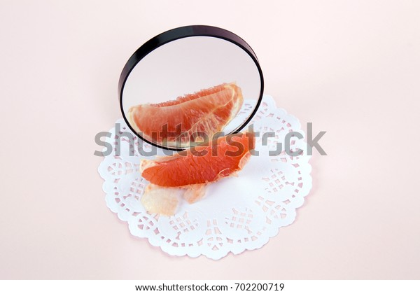 Minimalist and poetic composition of a grapefruit reflected in a mirror.