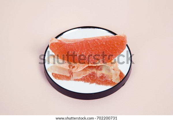 Minimalist and poetic composition of a grapefruit reflected in a mirror.Minimal color still life photography