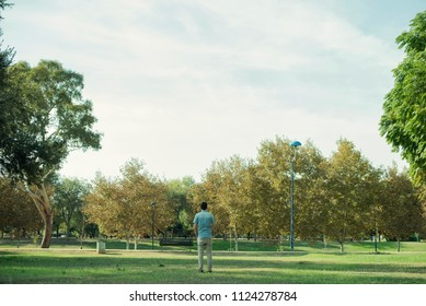 Minimalist portrait of man with his back to the distance in the middle of a landscape of a park or forest with many green trees and a large expanse of grass.