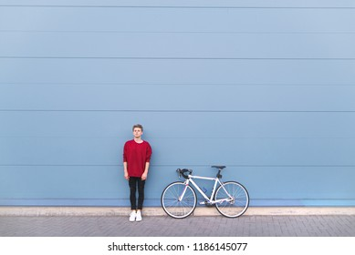 Minimalist portrait of a young man standing with a bike on a pastel blue background and looking into the camera. Stylish man with a bike. Sports concept.Wall. Copyspace