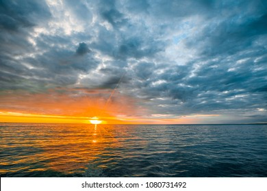 Minimalist seascape - stormy clouds over calm waters with sun touching the horizon