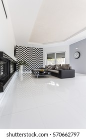 Minimalist spacious living room with black couch and patterned wallpaper