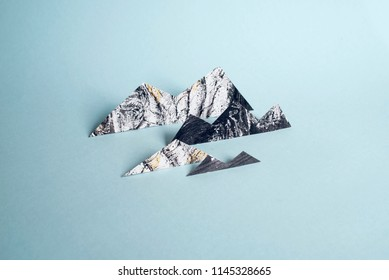 Minimalist still life of small mountains made of newspaper pieces and torn magazine pages. The background is light blue