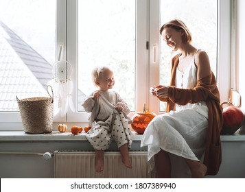 Minimalist style family with child preparing for Halloween. Happy mother and her little daughter sitting near window with carving pumpkin head jack lantern and halloween decoration at home.