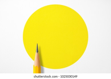 Minimalist template with copy space by top view close up macro photo of wooden yellow pencil isolated on white texture paper and combine with yellow circle. Flash light made smooth shadow from pencil.