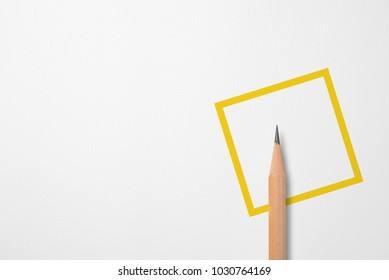 Minimalist template with copy space by top view close up photo of wooden pencil isolated on white paper and combination with yellow line square graphic. Flash light made smooth shadow from pencil.