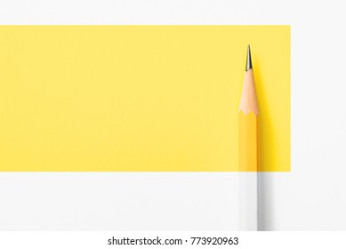 Minimalist template with copy space by top view close up macro photo of wooden yellow pencil put on yellow paper. Flashlight make difference between pencil and yellow paper by highlight and shadow.