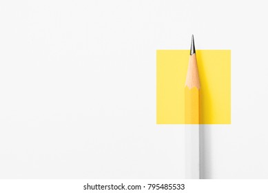 Photo of Minimalist template with copy space by top view close up macro photo of wooden yellow pencil isolated on white texture paper and combine with yellow square. Flash light made smooth shadow from pencil.