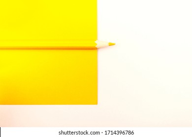 Minimalist template with copy space. Top view close up macro photo of wooden yellow pencil put on yellow paper. Flashlight make difference between pencil and yellow paper by highlight and shadow.