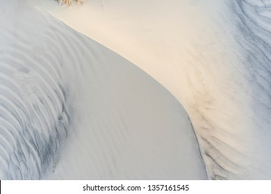Minimalist top view of beach dune with washboard patterns, curved ridge, and, at upper left, a hint of grass at sunrise, for background or element with natural, coastal, or marine motif
