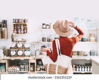 Petite fille de style végétalien minimaliste avec sac en osier et tasse de café en verre réutilisable sur fond intérieur de boutique zéro déchet. Femme faisant des courses sans emballage en plastique dans un supermarché sans plastique.