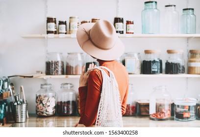 Jeune femme au style végétalien minimaliste avec un sac à filet en coton réutilisable sur fond de produits de la boutique zéro déchet. Acheter sans emballage en plastique dans un supermarché sans plastique.