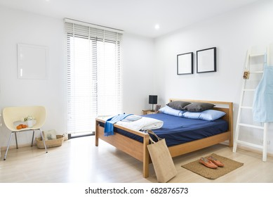 Minimalist white bedroom, blue bed decorated with white staircase, frame and chair.