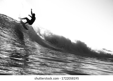 Minimalist white and black surf scene. A surfer rides a small wave along a point break with few other people in the water. A peaceful simple beach background of the ocean