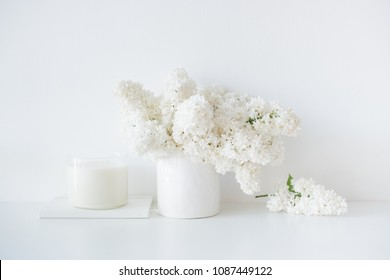 Minimalist white home decor, fresh lilac flowers bouquet in vase