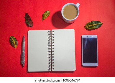 Minimalist workspace on top view with copy space. A cup of coffee, blank notebook, smartphone ,silver pen on red background