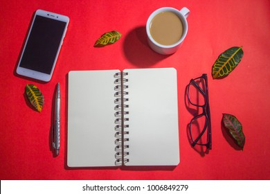 Minimalist workspace on top view with copy space. A cup of coffee, blank notebook, smartphone, black spectacles ,silver pen on red background