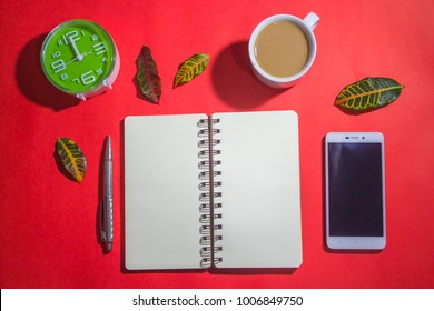 Minimalist workspace on top view with copy space. A cup of coffee, blank notebook, smartphone ,alarm clock, silver pen on red background