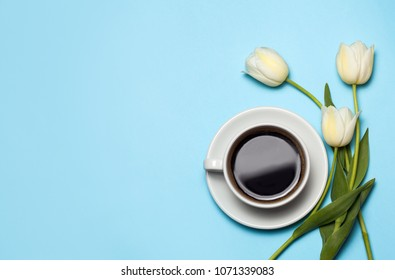 Minimalistc picture of cup of coffee and white tulips on blue background. Spring coffee concept. top view, flat lay.