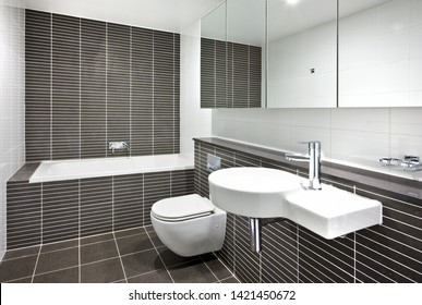 A minimalistic bathroom featuring a bathtub, a sink, a wall-mount toilet seat, and mirrors