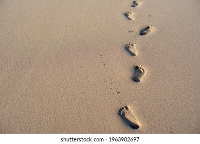 Minimalistic beach scene of two sets of foot prints in sand. Horisontal version of the photo