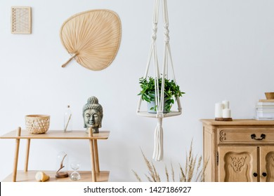 Minimalistic boho interior with design and handmade macrame shelf planter hanger for indoor plants, wooden furnitures, elegant accessories ,rattan basket and leaf. Cozy home decor. White walls.