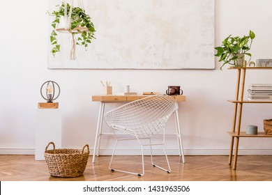 Minimalistic boho interior with design and handmade macrame shelf planter hanger for indoor plants, wooden desk, armchair, bamboo shelf and elegant accessories. Stylish home decor. White walls.