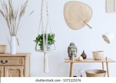Minimalistic boho interior with design and handmade macrame shelf planter hanger for indoor plants, wooden furnitures, elegant accessories ,rattan basket and leaf. Cozy home decor of living room.