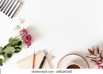 Minimalistic border frame made of flowers, mug of coffee and stationery on white background