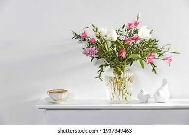 A minimalistic bouquet of white tulips, pink eustoma, hyacinth, eucalyptus in a fluted glass vase on a white panel of an artificial fireplace. Cup of tea, faience figurines of a two birds