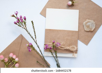 Minimalistic card mockup with Chamelaucium branch, tender flower, craft envelope, violet blossom, flat lay, top view
