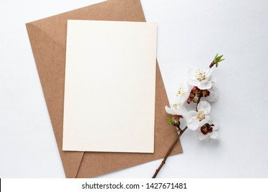 Minimalistic card mockup with cherry branch, flower, craft envelope, blossom, flat lay, top view