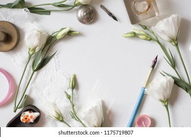 Minimalistic card mockup with eustoma, white flower, craft envelope, flat lay, top view white eustoma flowers. Workspace. Wedding invitation cards,  lisianthus with copy space