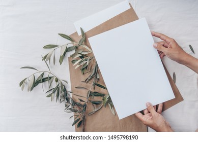 Minimalistic card mockup with olive branches, hands. Flat lay, top view. Mockup card with plants. Wedding invitation card with environment and details