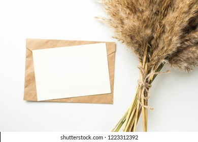 Minimalistic card mockup with reed flower, craft envelope, blossom, flat lay, top view