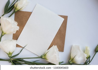 Minimalistic card mockup with  white eustoma flowers. Workspace. Wedding invitation cards, craft envelopes, lisianthus with copy space. Overhead view. Flat lay, top view