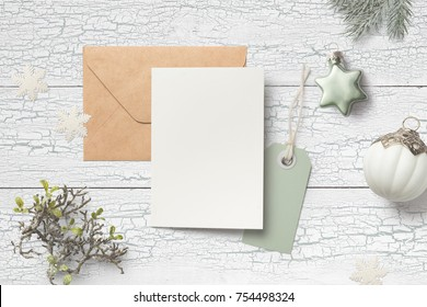 minimalistic christmas card mock up with green fir branches, baubles, card, envelope, hangtag and glitter snowflakes