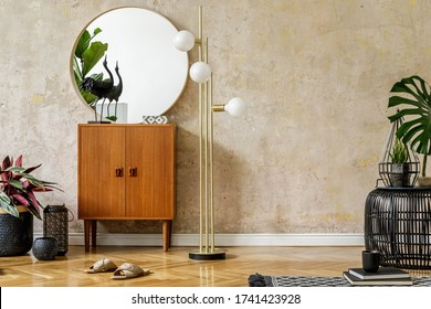 Minimalistic composition at living room interior with design commode, tropical leaves, gold lamp, copy space, carpet, rattan pouf and elegant personal accessories in stylish home decor.