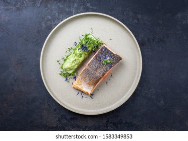 Minimalistic design salmon fish filet glazed with avocado and wasabi creme in a sliced cucumber as top view on a modern design plate decorated with herbs with copy space