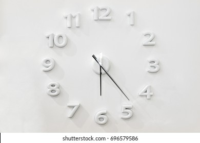 Minimalistic design of wall clock with white numbers