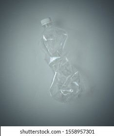 Minimalistic ecological concept. Crumpled plastic bottle on gray background. Environmental plastic pollution