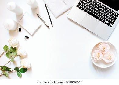Minimalistic feminine workplace with laptop keyboard, pen, pencil, white candles, notebook, office clips and roses in flat lay style. White background, top view, frame