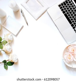 Minimalistic feminine workplace with laptop keyboard, pen, white candles, notebook and roses in flat lay style. White background, top view, frame
