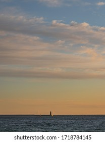 Minimalistic fine art photography of a small ighthouse at the end of the concrete port breakwater. Photographed during sunrise with busy sky covered in clouds.