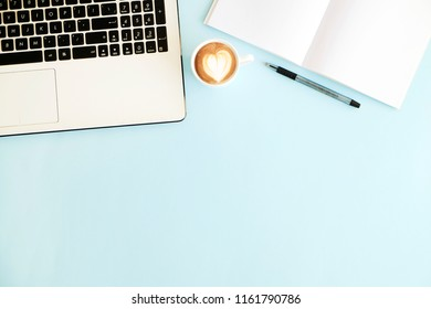 Minimalistic flat lay composition of black & white laptop computer keyboard, cell phone, coffee cup, blank page notebook on baby blue surface desk table background. Workspace top view, copy space.